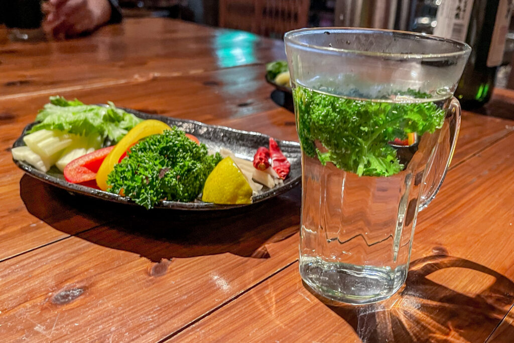 A plate of various infusions to add to a shochu cocktail, including celery, bell peppers, parsley, lemon, ginger and chili, next to a glass of parsley-infused shochu.