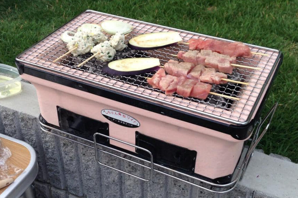A Japanese shichirin grill with onion, eggplant and skewered meat grilling on top.