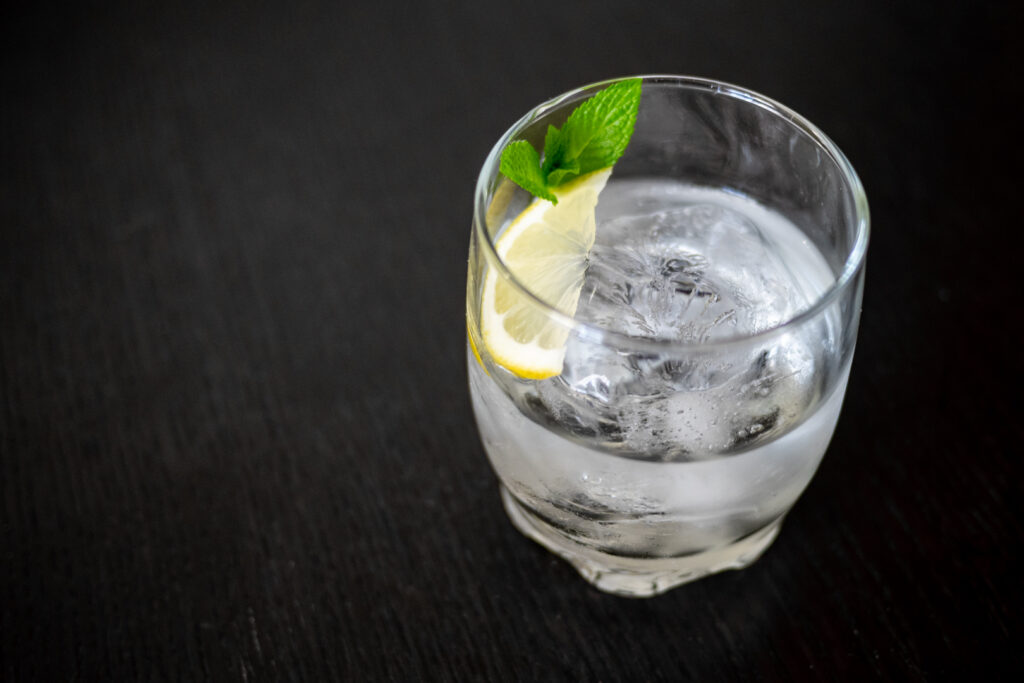 Shochu served mizuwari style in a clear glass with ice and water, along with some lemon and mint sits on a dark wooden counter top.