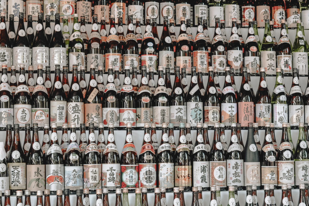 Five tiered shelves completely covered with various types of shochu bottles. © Julien Miclo.