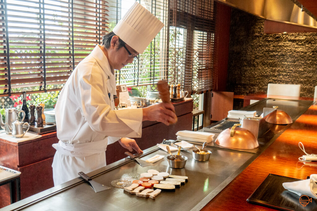 A Japanese chef with a white chef's jacket and tall hat is seasoning teppanyaki vegetables over a Japanese teppan grill.