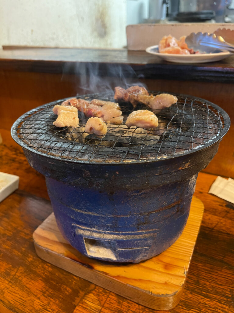 A clay pot with charcoal inside and meat cooking on the metal grill placed on top (this type of Japanese grill is known as a shichirin in Japanese). Photo by Saki Inoue.
