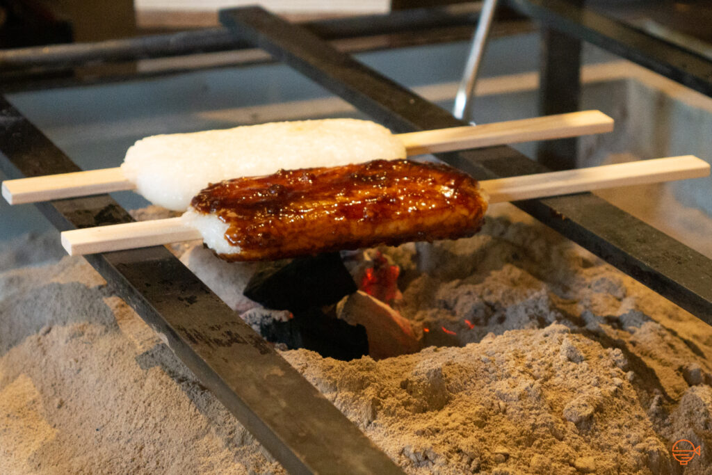 Two long mochi on wooden sticks are resting atop two metal bars on the hibachi, being grilled over the hot charcoal and ash.