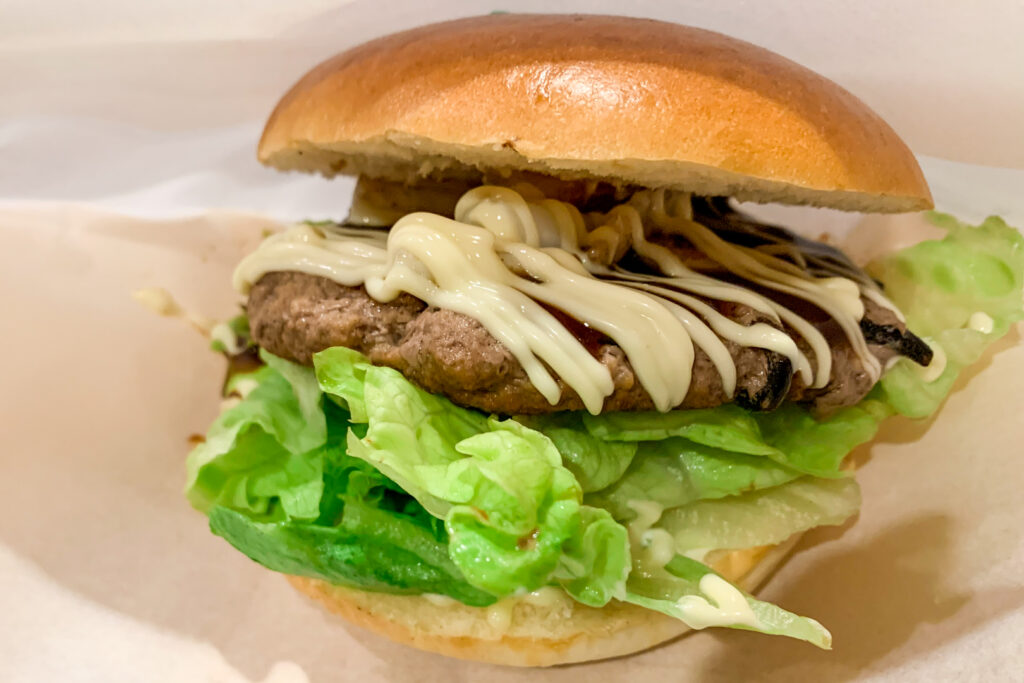 A Tsushima Burger - a thick meat patty mixed with hijiki seaweed and topped with grilled squid and mayonnaise, plus lettuce in a bun,