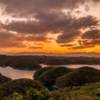An orange and pink sunset over the vegetated hills of Tsushima Island. © Lisa Wallin