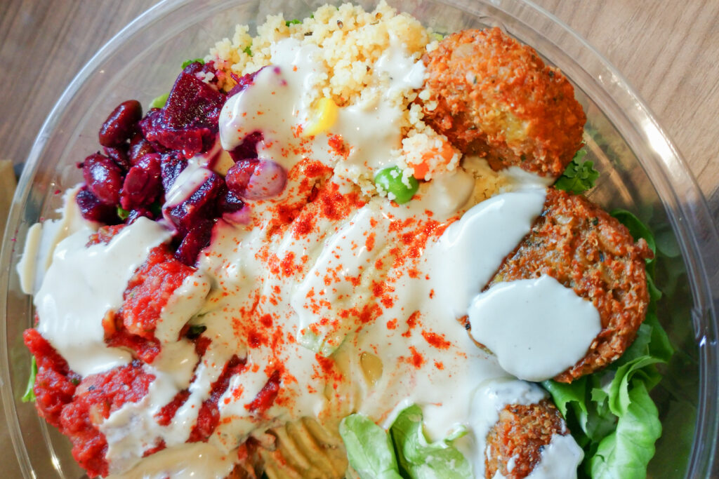 A close up shot of a falafel salad bowl with various colorful salad items (including beetroot, corn, lettuce and pickles), falafel and hummus. Photo by author, Kaori S.