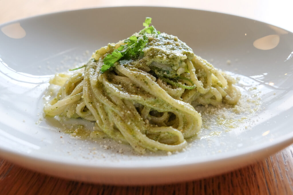 A serving of pesto spaghetti on a large white lipped plate. Photo by author, Kaori S.