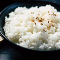 A black bowl filled with fluffy white Japanese rice and some sesame seeds sprinkled on top. © Mgg Vitchakorn.