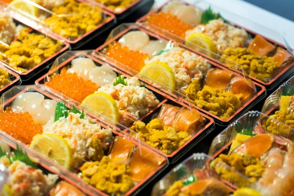 Rows of bento boxes at a store with sushi grass in them.