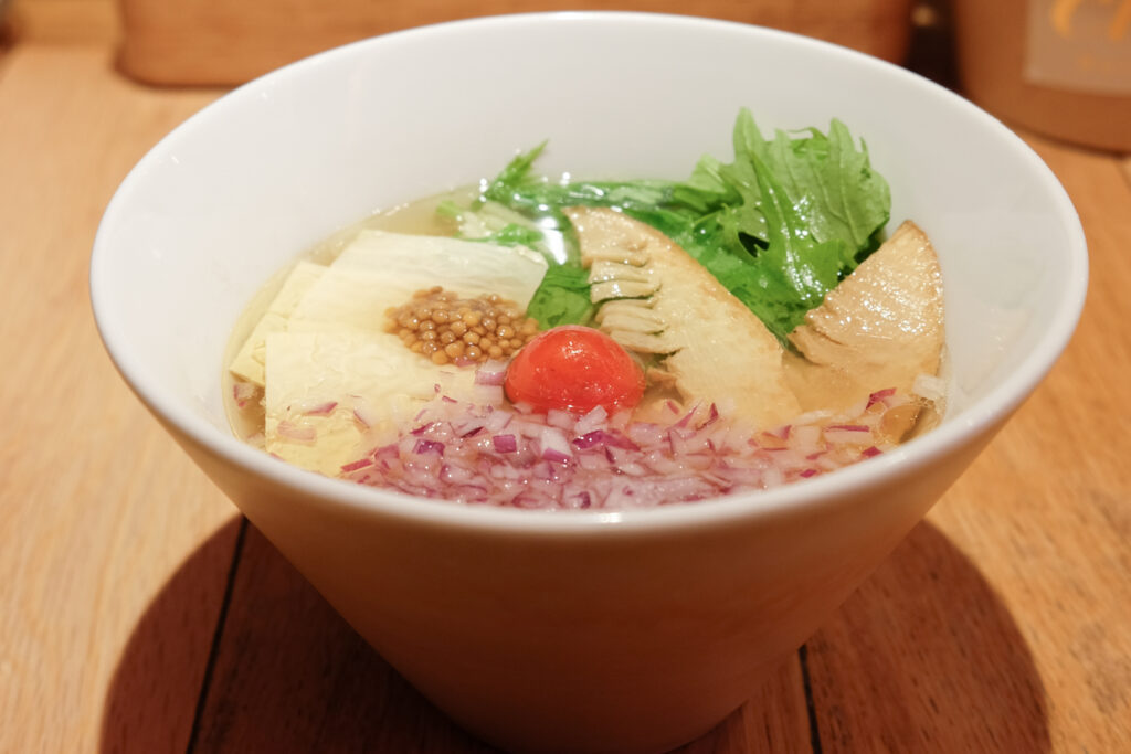 A bowl of vegan ramen with seasonal veggies from Chipoon in Harajuku, Tokyo. Lettuce, tomato and chopped red onion add color to the light salt-based and lemon-flavored broth.