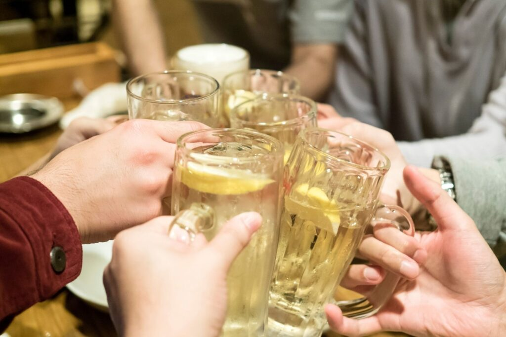 Five people each hold a glass of chu hi with a slice of lemon in it at a bar, clinking their glasses together at the center of the table in a 'cheers' motion.