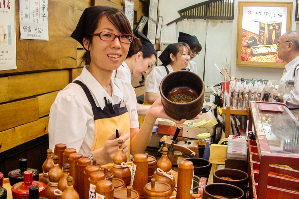 A female staff member at Yagenbori Shichimi Togarashi in Asakusa (Tokyo), faces a wooden bowl towards the camera to show the custom blend she is making for the author. Behind her are three other staff members working; one is assisting an older man in the background. In the foreground are variously-shaped wooden containers for storing your 7 spice mix.