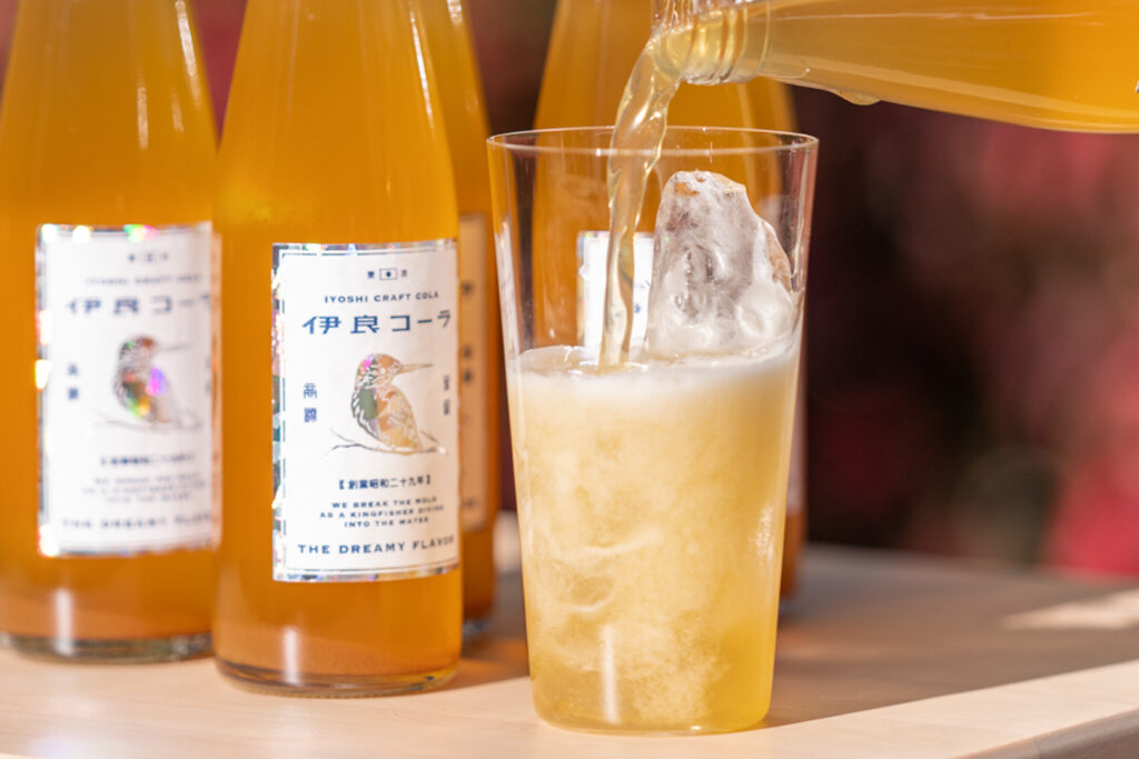"""In the background, bottles of Iyoshi's """"The Dreamy Flavor"""" Craft Cola are lined up, while in the foreground a glass is being prepared to drink with the orange liquid being added to a glass of ice and possibly soda water."""