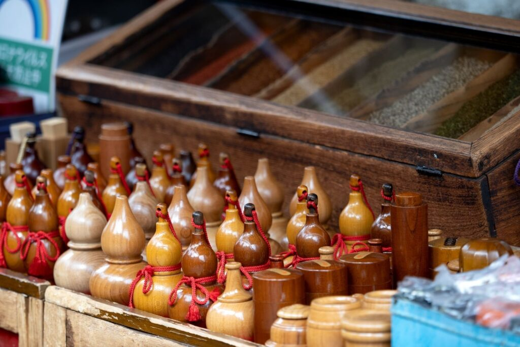 A stall selling various wooden containers used to store this Japanese spicy condiment. A large wooden case with a glass top sits behind the containers with seven different spices.