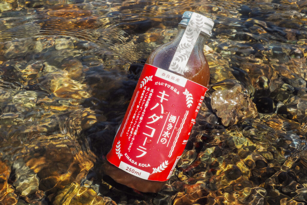 A bottle of brown-colored Kihada Cola concentrate with a red label sits partially in the water and against a rock of a shallow river bed with crystal-clear water.
