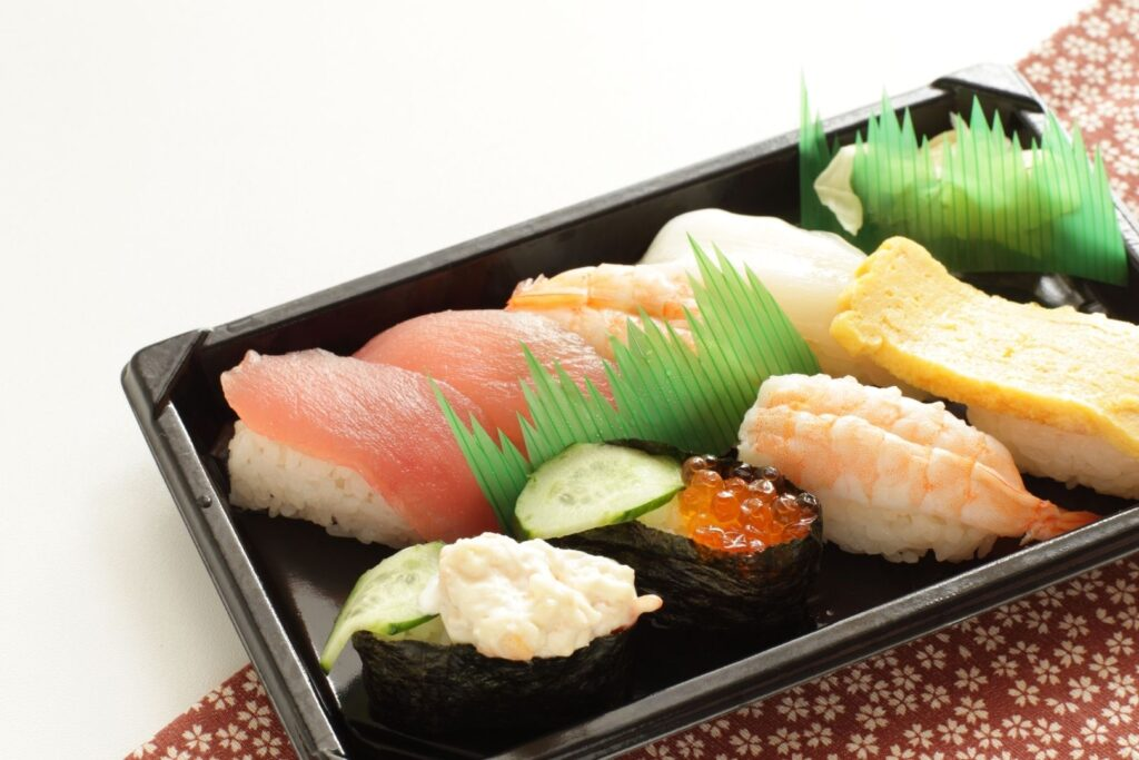 A sushi bento with sushi grass separating the two rows of sushi items and also the pickles.