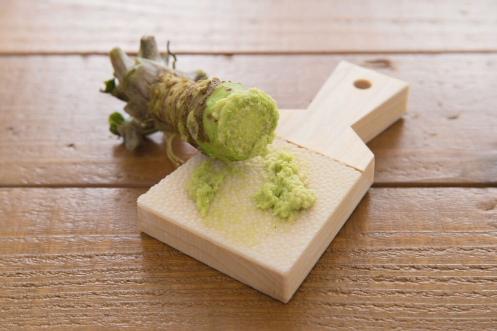 A rhizome rests upon a traditional shark skin grater with a small amount of wasabi paste that has been freshly grated.