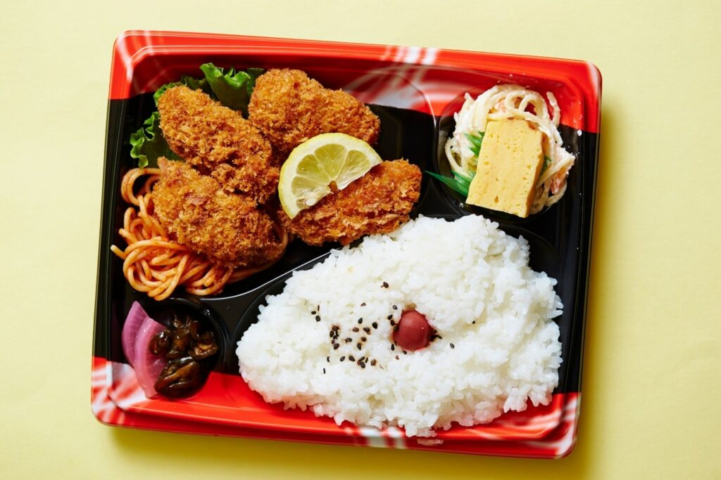 A classic Japanese store-bought bento box featuring fried oysters. The egg and the saucy salad are separated by plastic sushi grass.