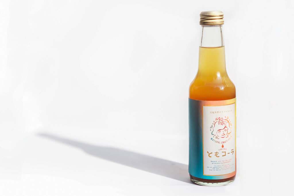 A tall, sleek bottle of orange-colored Tomo Cola is to the right of frame and casting a long shadow against the white surface it's sitting on.