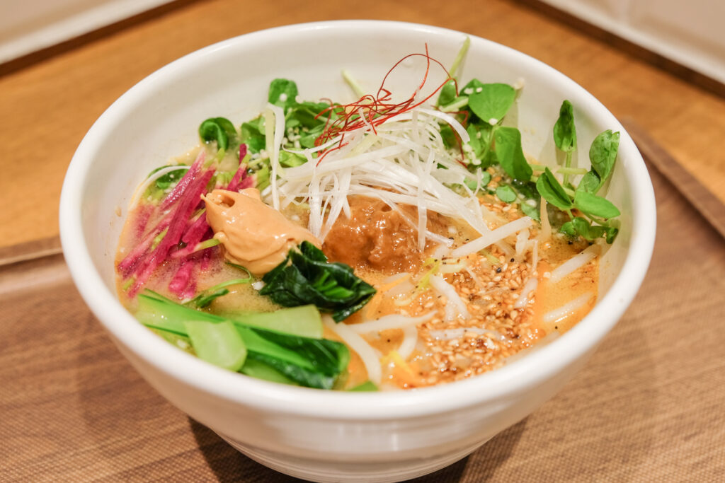 A bowl of T's Tan Tan Golden Sesame Vegan Tantanmen - with its golden broth, and pops of green, red and white veggies.