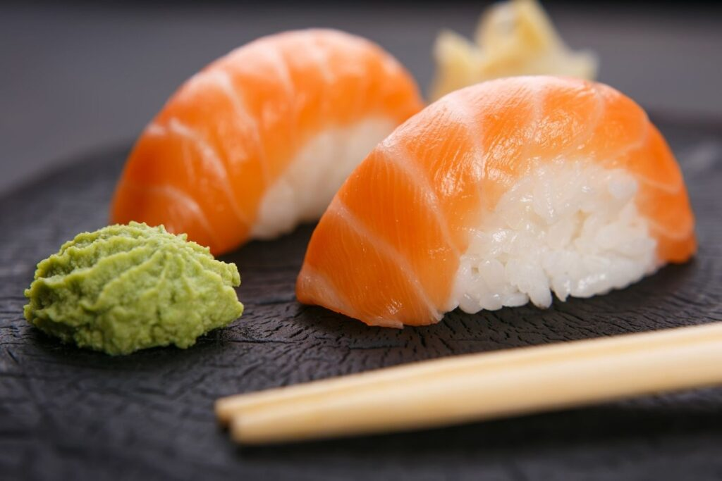 To the left is a blob of green wasabi paste and to the right there are two pieces of salmon-topped sushi (nigirizushi) with pickled ginger in the background. A pair of wooden chopsticks are laying flat on the table surface in the foreground.