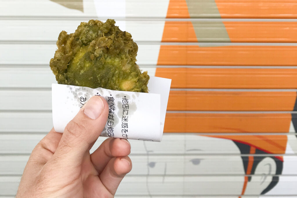 A hand holds up a green-colored 'age manju' against a shop's shutters with a mural on it. The age manju has been sold with a small piece of paper for holding the snack at the bottom without getting burnt or oily fingers.