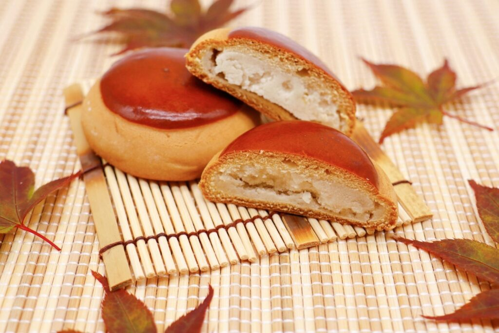 Two chestnut manju on a bamboo place mat surrounded by autumn maple leaves. One of the manju is cut in half showing the chestnut filling.