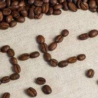 Coffee beans are spread out over a beige muslin table cloth. In the center a space has been cleared and the Japanese word for coffee (kohii) is written out in beans in katakana.
