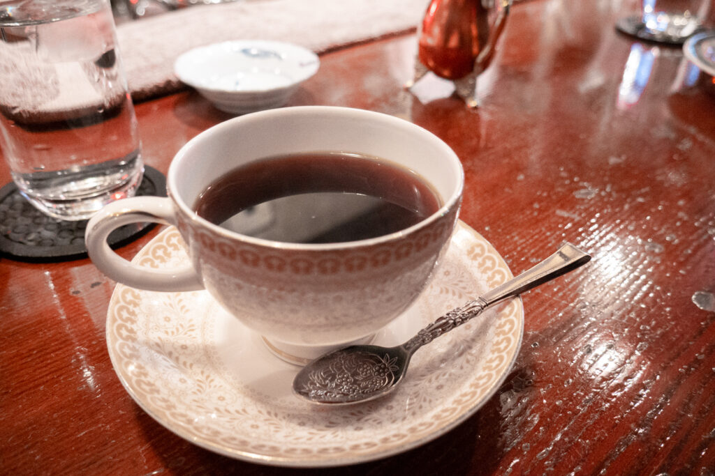 Coffee Japan - a cup of coffee in Japan in a small cup with a brown and gold design on a matching saucer with the handle to the left. A fully engraved silver spoon sits in front of the cup with the handle to the right.