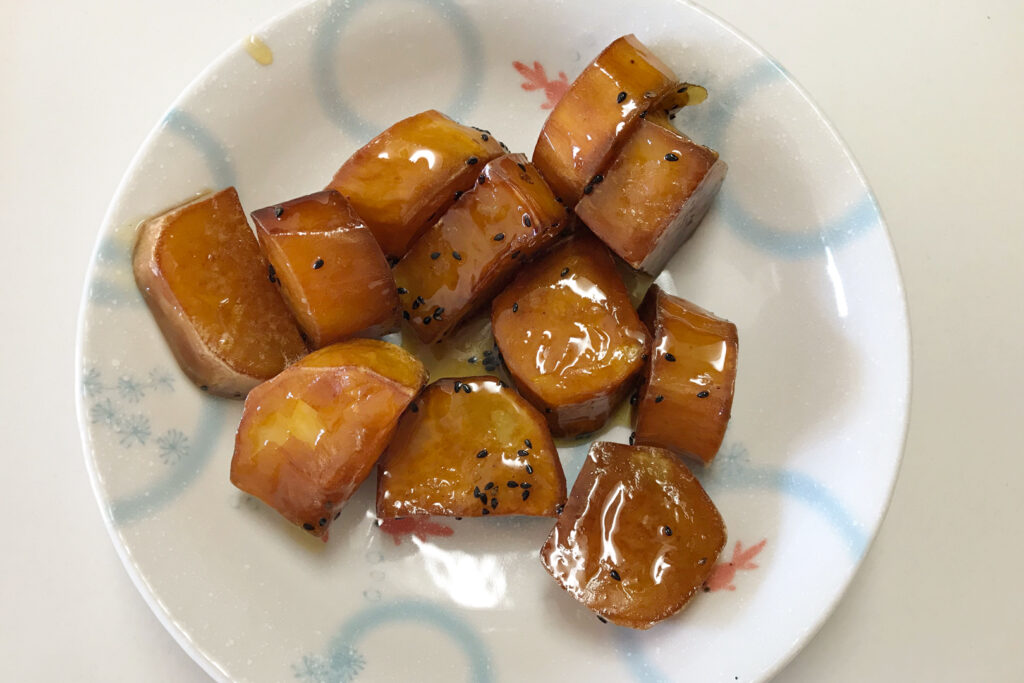 A white plate with a light blue ring pattern on it. On the plate is sweet potato fried in oil and covered in honey.
