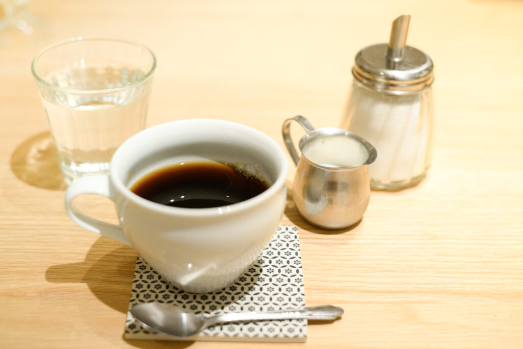 Coffee in Japan at a cafe. A small white cup is served with the handle to the left and a silver spoon in front with the handle to the right. They both sit on a blue and white patterned coaster. Sugar, milk and a glass of water are also on the table.