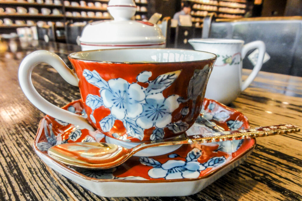 A typical way coffee in Japan is served. A small, intricately designed Japanese coffee cup - red with a blue and white flower design - positioned with the handle to the left and sitting on a matching saucer. A dsinty gold spoon with the handle to the right in on the saucer in front of the cup.