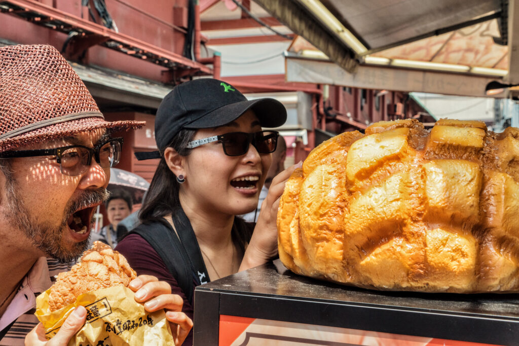 At the counter of the store, a man dramatically opens his mouth to pose for a fun photo of him about to devour his just-bought melon pan. The woman next to him looks at the massive fake melon pan sitting on the countertop (as an example for customers) with a look of glee and wonderment.