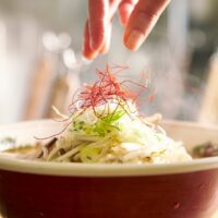 A hand can be seen gently adding saffron to the top of a steaming bowl of miso ramen.