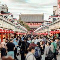Looking down a crowd-filled Nakamise dori with little shops on either side and Sensoji Temple down the end.
