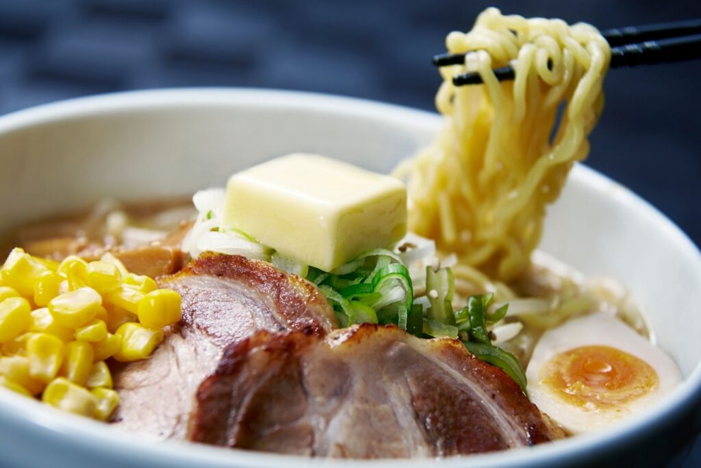 A bowl of miso ramen in Sapporo with corn, charshu sliced pork, egg, spring onions and a square piece of butter on top. Chopsticks are holding up noodles from the bowl from the right.