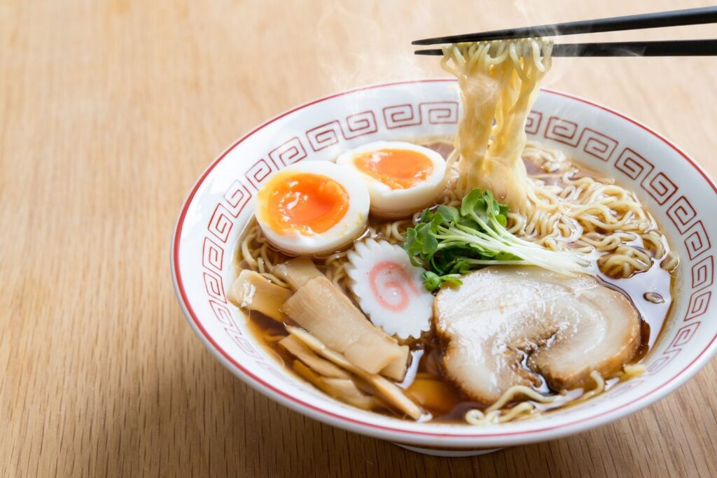 A bowl of shoyu ramen (soy sauce base) with egg, sliced pork, fermented bamboo shoots, narutomaki and some greens as toppings. Chopsticks can be seen holding up some noodles from the right.