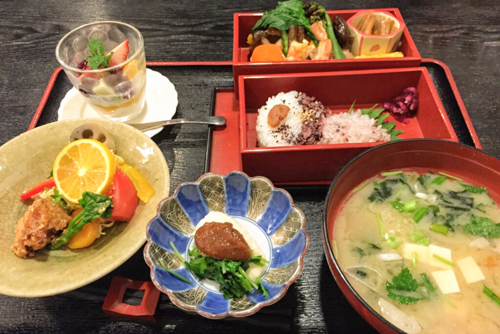 An example of the Hanaguruma bento at Meshi-ya Mizu. In the front row, from left to right, is a side salad with vegetables, next is a small bowl of pickles and miso paste, followed by a bowl of miso soup with tofu. Behind it in the second row are two boxes that have been unstacked from one another - one has rice and pickles, and the other has the main of the day. To the left is a dessert with fruit.