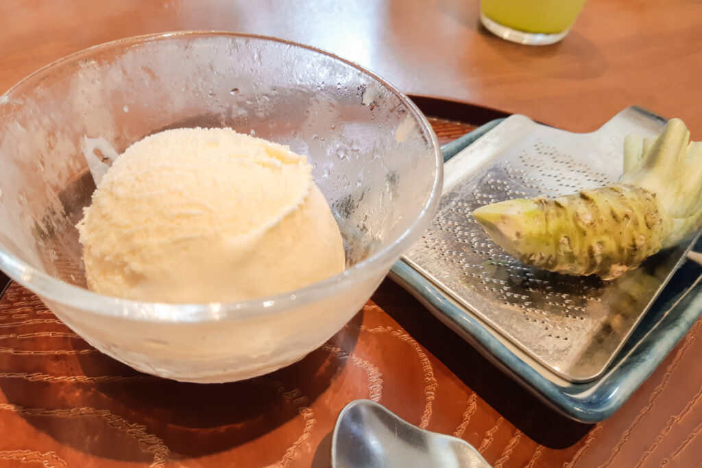 To the left of frame is a chilled glass bowl of vanilla ice cream, and to the right is a wasabi rhizome (thickened stem) on top of a metal grater ready to be grated by the customer and enjoyed with the ice cream.