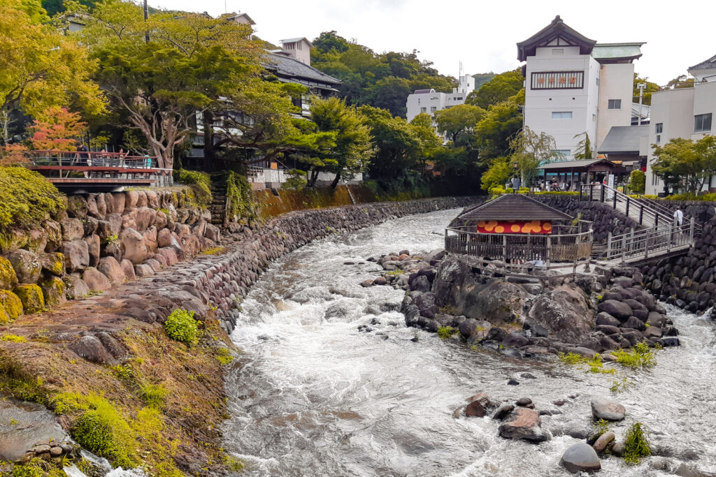 A view of the center of Shuzenji town with the Katsura River winding around the historic Tokko-no-Yu outdoor bath (no longer accessible to the public).