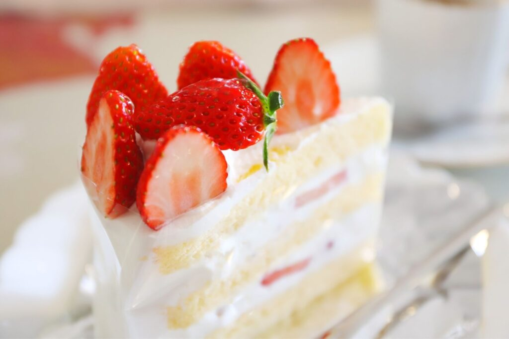 A slice of three layered strawberry shortcake with yellow sponge cake, cream and strawberries between the layers, and more cream and strawberries on top.