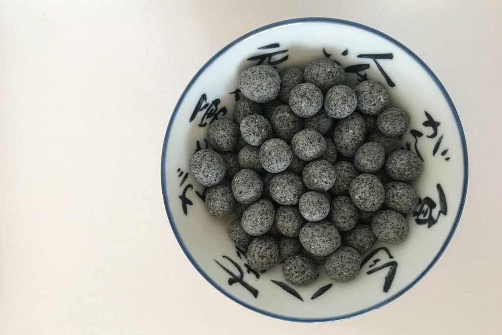 A white bowl with blue Japanese characters on it and a blue lip is partially filled with round black Kurogoma-mame beans.