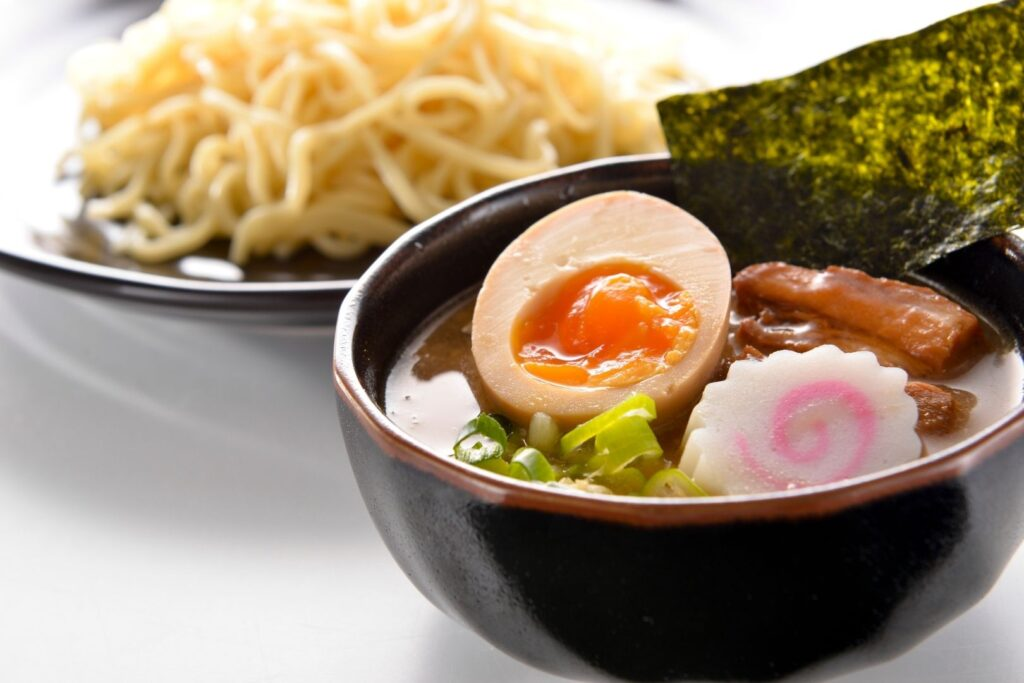 Tsukemen - a type of ramen where the noodles are served separately to the broth. A plate of ramen noodles can be seen in the background, while a bowl of broth with various toppings including a piece of nori (dried seaweed) sticking up at the side, can be seen in the foreground.