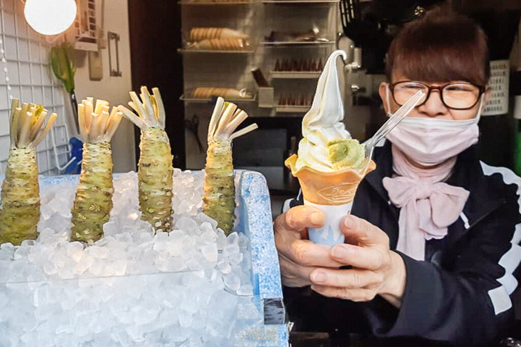 To the left is an ice-filled styrofoam box with four wasabi rhizomes (thickened stems) standing up in it. To the right, a server is handing over a soft-serve ice cream cone with a spoon and a dollop of freshly-grated wasabi.