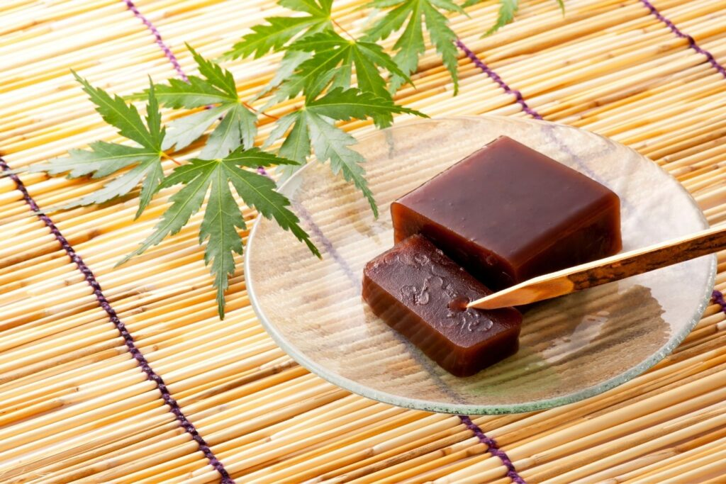 A dark-brown rectangular slab of yokan with one slice cut off the end and resting on the clear plate beneath it. The plate is sitting atop a bamboo placemat and green momiji leaves are sitting behind it as seasonal decoration.