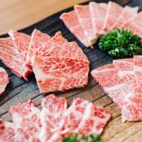A variety of slices of raw a5 wagyu are arranged on a large plate with parsley as a garnish.