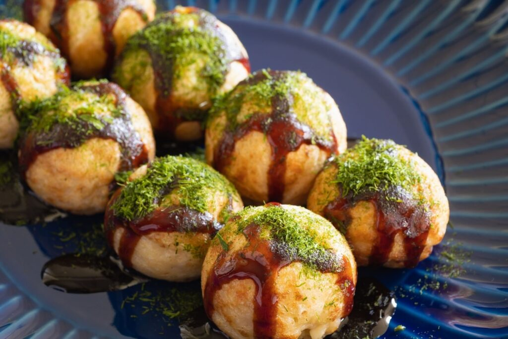 A serving of takoyaki octopus balls with green aonori seaweed powder sprinkled on top.