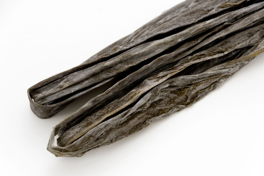 Two long pieces of dark, dried kombu folded in two on a white surface.