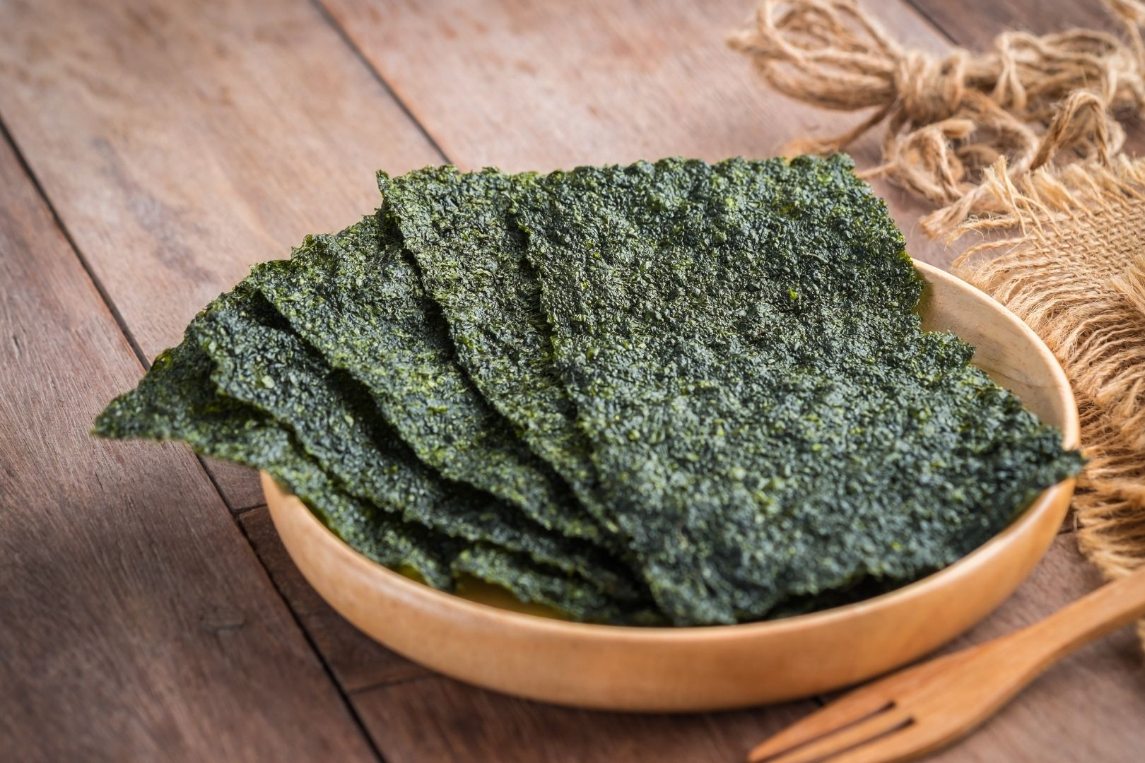 Edible Seaweed: Five sheets of nori seaweed fanned out in a wooden bowl on a wooden table. In front is a wooden fork and to the right is a natural-fiber placemat.