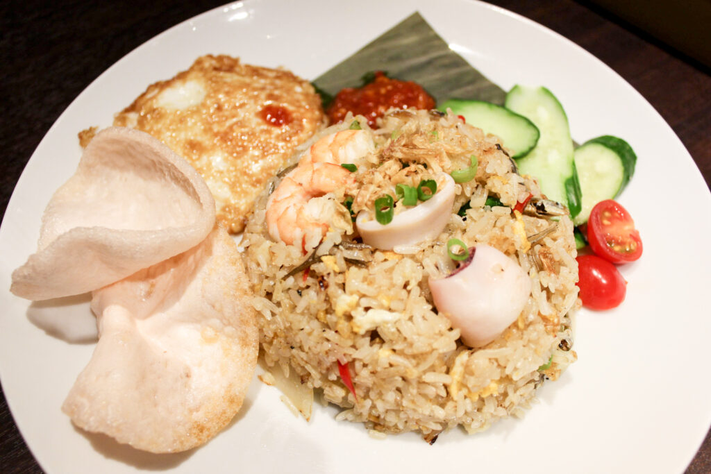 Halal restaurants in Tokyo - a plate of nasi goreng at Malay Asian Cuisine, fried rice with seafood plus egg, sambal, cucumber, cherry tomato and prawn crackers.
